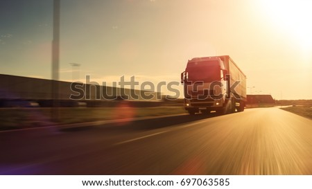 White Semi Truck with Cargo Trailer Attached Drives on the Empty Road. Industrial Warehouses by the Sides of the Highway. Sunset. Blur motion. #697063585