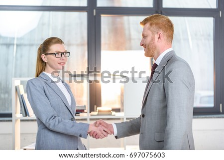 businesspeople shaking hands and looking at each other #697075603