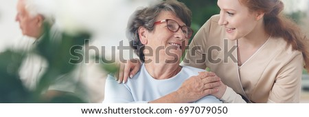 Professional helpful caregiver comforting smiling senior woman at nursing home #697079050