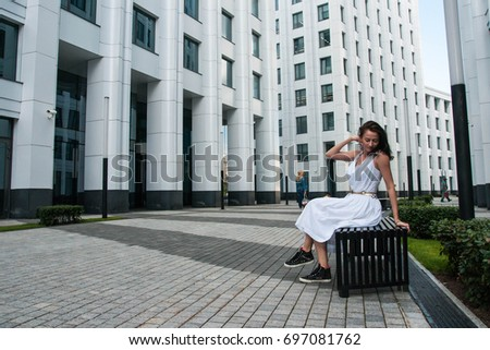 Portrait of a beautiful Brunette in white dress sitting on a bench #697081762