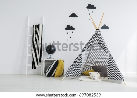 Stylish,patterned teepee with a white teddy bear lying inside it, in a minimalist. scandinavian kid bedroom #697082539