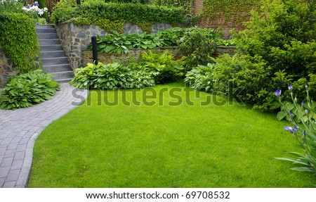 Garden stone path with grass growing up between the stones #69708532