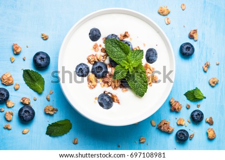 Greek yogurt granola and blueberries on blue table top view. Healthy food nutrition, snack or breakfast. #697108981