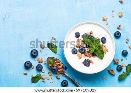 Greek yogurt granola and blueberries on blue table. Top view copy space. Healthy food, snack or breakfast. #697109029