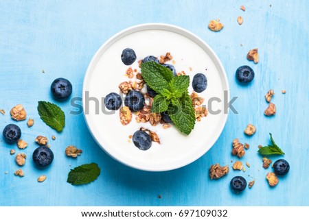 Greek yogurt granola and blueberries on blue table top view. Healthy food nutrition, snack or breakfast. #697109032