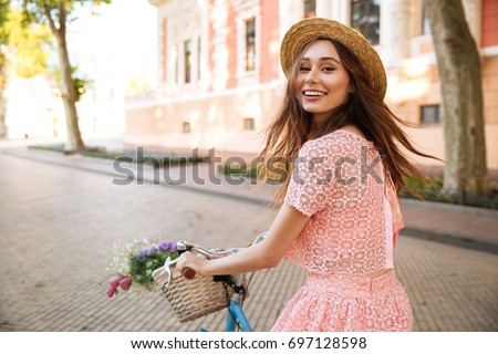 Smiling happy girl in dress and hat riding retro bicycle on a city street and looking at camera #697128598