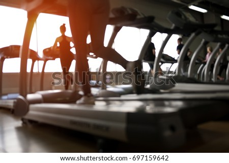 Row of treadmills in modern fitness center, closeup. Blurred picture of Running people. Gym equipment.