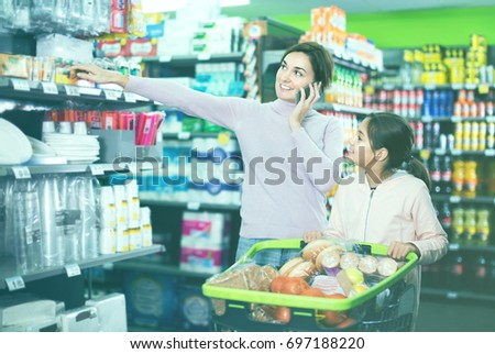 Young smiling glad friendly female shopper talking on phone being with teenager in supermarket #697188220