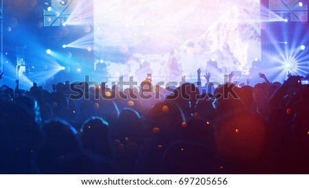 Crowd at concert - Cheering crowd in front of bright colorful stage lights #697205656