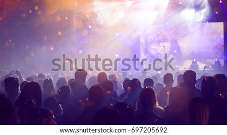 Crowd at concert - Cheering crowd in front of bright colorful stage lights #697205692