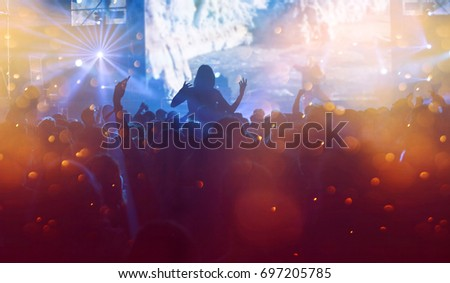 Crowd at concert - Cheering crowd in front of bright colorful stage lights #697205785