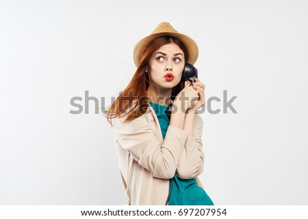 Stylish woman in a hat holds a telephone receiver on a light background                                #697207954