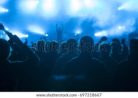 Crowd at concert - Cheering crowd in front of bright colorful stage lights #697218667