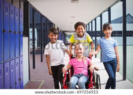 Cute disabled pupil smiling at camera with her friends against empty corridor at school #697256923