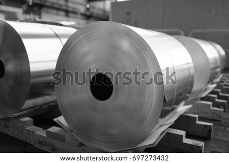 final coils of aluminum foil after slitting on wood, black and white photo Royalty-Free Stock Photo #697273432