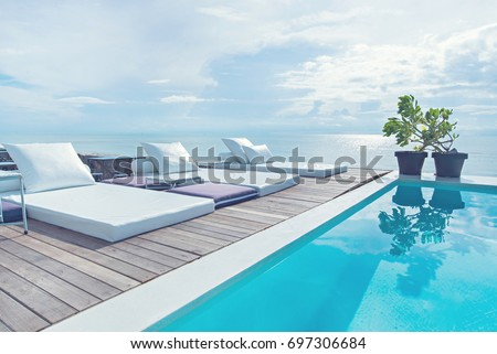 The edge Luxury swimming pool with white fashion deckchairs on the beach., Exterior design. Royalty-Free Stock Photo #697306684