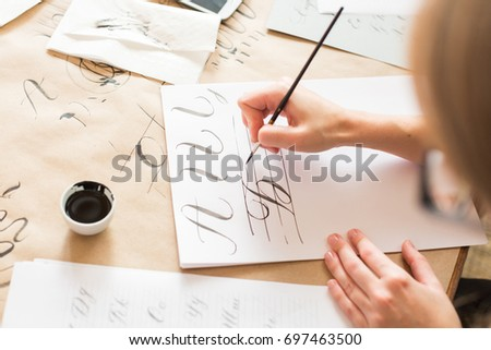 calligraphy, handwriting, technique concept. woman with beautiful elegant hands inscribing capital russian letters carefully in italic type with black ink and thin brush, drawing #697463500