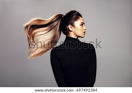 Studio shot of stylish young woman with flying hair against grey background. Female fashion model with long hair. #697492384