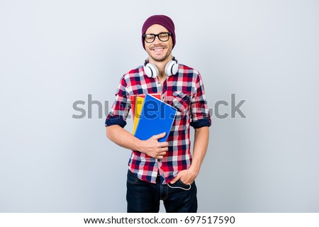 Smiling young nerdy stylish student hipster is standing with books on pure background in black trendy glasses and hat, casual bright checkered outfit