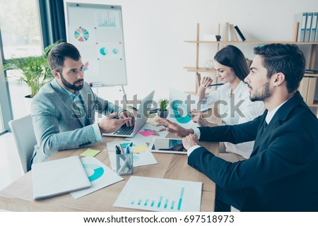 Business meeting, partners are discussing the decisions at the light modern office. Men are serious and concentrated, the guy is asking about data, gesturing, lady is cheerful #697518973