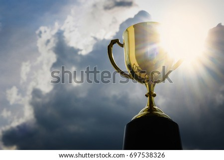 Gold cup winner trophy on sky background , Award winning trophy for a champion in a competition and best business. Concept for winning or success #697538326