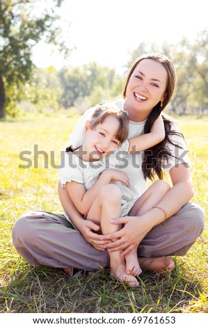 beautiful young mother and her daughter in the park on a sunny autumn day #69761653