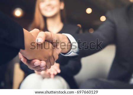 Businessmen making handshake with his partner in cafe - business etiquette, congratulation, merger and acquisition concepts Royalty-Free Stock Photo #697660129