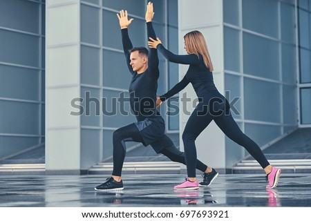 The athletic fitness couple is stretching over modern building background. Full body image. #697693921