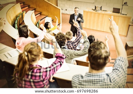 Rear view of students raising hands with teacher in college lecture hall Royalty-Free Stock Photo #697698286