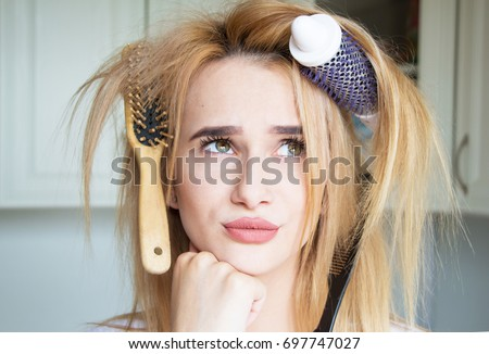 Young girl trying to comb her hair #697747027