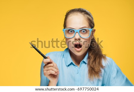 Female student with glasses on a yellow background                                #697750024