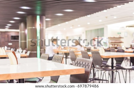Modern interior of cafeteria or canteen with chairs and tables Royalty-Free Stock Photo #697879486