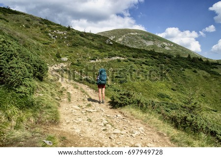A woman is traveling in the mountains #697949728