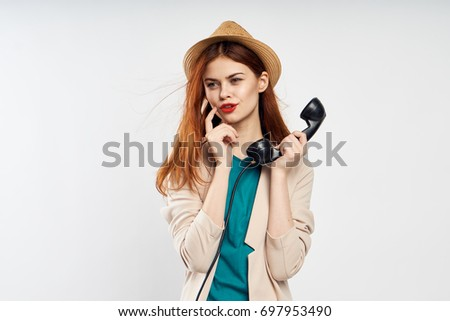 Beautiful woman in a hat thoughtfully holds a fixed telephone on a light background                                #697953490