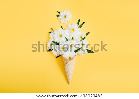 Waffle cone with chamomile flower bouquet on yellow background. Flat lay, top view floral background. #698029483