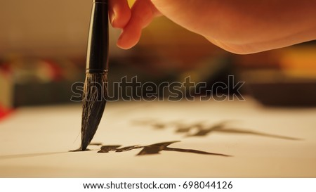Close up on hand holding brush while writing calligraphy