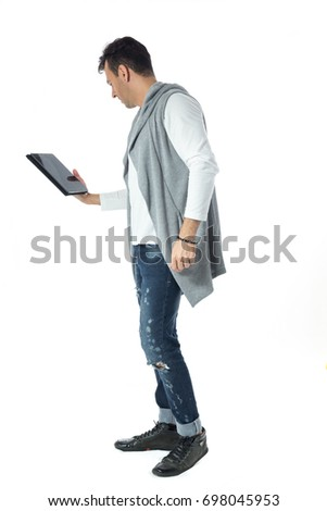 Man on his back using a tablet and surfing the internet. Handsome brazilian wearing gray and white clothes, neutral. #698045953