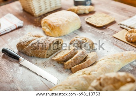 Fresh bread slice and cutting knife on rustic wooden table #698113753