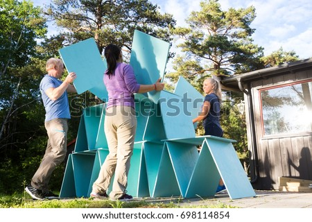 Friends Building Pyramid With Wooden Planks In Forest #698114854