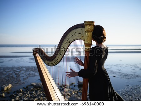 Portrait of a girl with a harp on a blue sky background and the sea.  Royalty-Free Stock Photo #698140000