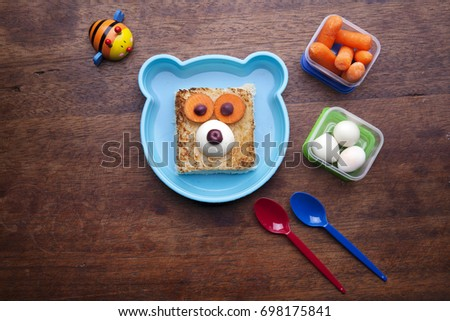 School lunch box snacks for kids over wooden background. Back to school. Top view. Healthy snack option for moms. Cute food art creative concepts. Bow with carrots, eggs and bear tasty sandwich. #698175841