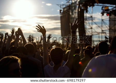 Silhouette of girl at Outdoors Music Festival at sunset Royalty-Free Stock Photo #698179297