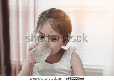 portrait of little girl drinking cold water, filtered tones #698222566