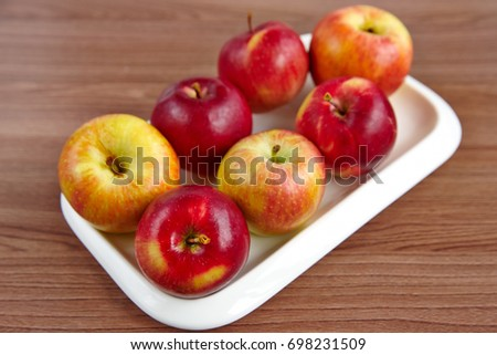 A plate with apples on a wooden table #698231509