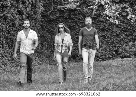 people or friends pretty girl and two bearded handsome man with beards walk outdoors on natural background #698321062