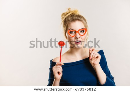 Happy blonde woman holding carnival accessories on stick fake red lips and paper heart shaped glasses, having fun. On grey wall background #698375812