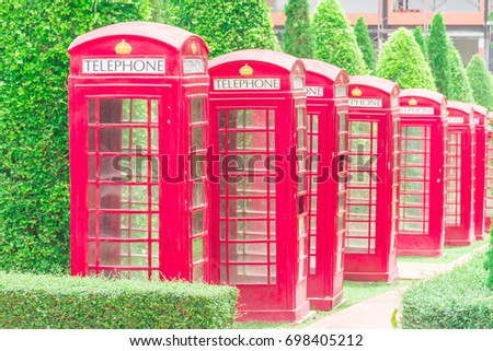 Red telephone booths along with the road with green pine trees background. #698405212