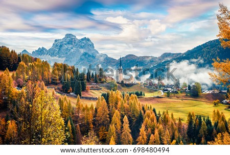 Foggy autumn view of Parrocchia Di Selva Cadore church. Great morning scene of Dolomite Alps, Cortina d'Ampezzo, southern Alps in the Veneto region of Northern Italy, Europe.