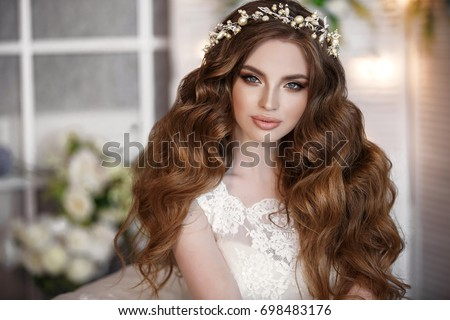 Gorgeous beauty young bride portrait. Beautiful bride with wedding makeup and jewelry wreath on long curly hair. Bridal fashion model with blue eyes posing in interior.  Royalty-Free Stock Photo #698483176