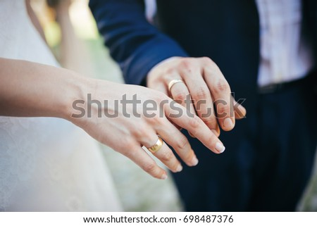 Wedding rings on the hands of the groom and the bride  #698487376